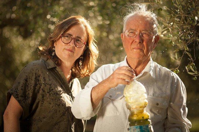 U padre con in mano una bottiglia d'olio e la figlia accanto