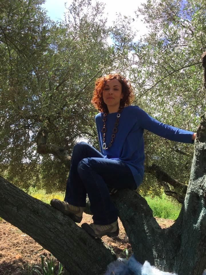 Una donna arrampicata su un olivo