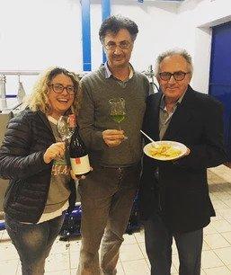 Tre oersone mostrano vino, olio e pasta