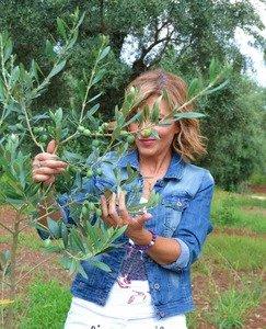 Una donna nascosta dai rami di un olivo