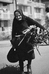 Una vecchia donna trasporta una fascina di legna